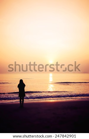 silhouette of woman alone and wave on the beach with sunset in the sea, blurred