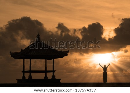 Silhouette of woman and outdoor pavilion during sunset at Bali beach, Indonesia - stock photo