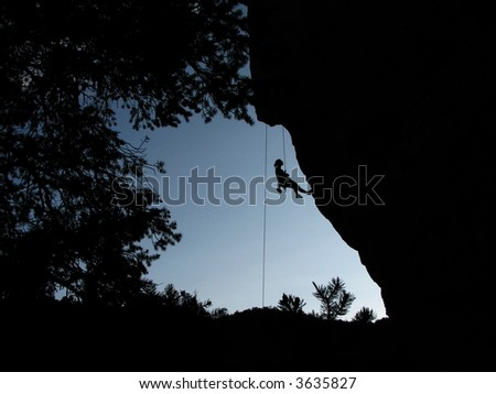 silhouette of woman climber resting while climbing an overhanging cliff framed by the cliff and trees - stock photo