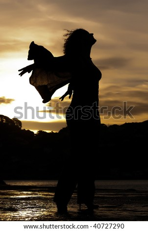 Silhouette of woman dancing with sunset in background