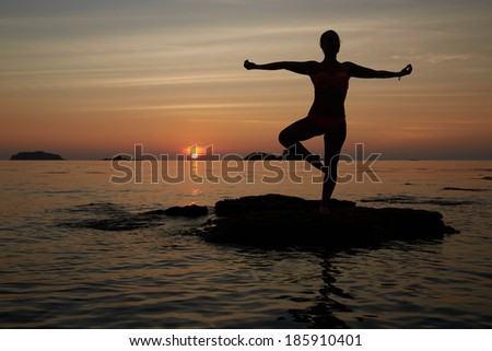 silhouette of woman doing yoga during sunrise on the beach