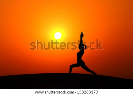 Silhouette of woman doing yoga meditation during sunset with natural golden sunlight on mountain. - stock photo
