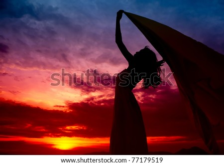 Silhouette of woman enjoy the sunset - stock photo