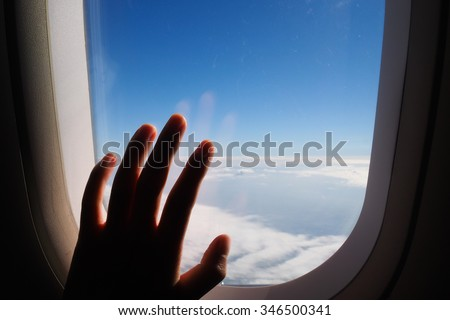 Silhouette of woman hand over the window of airplane. Clouds and sky as seen through window of an aircraft, air plane. - stock photo