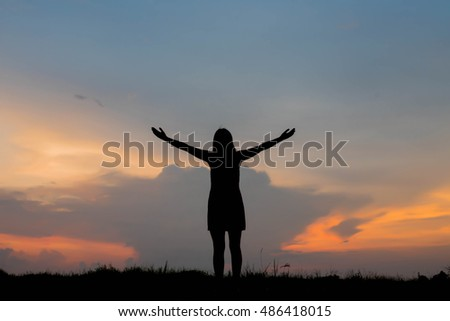 silhouette of woman happy alone at  sunset