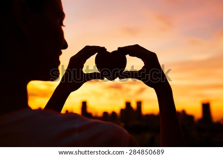 Silhouette of woman holding heart in the city.  - stock photo