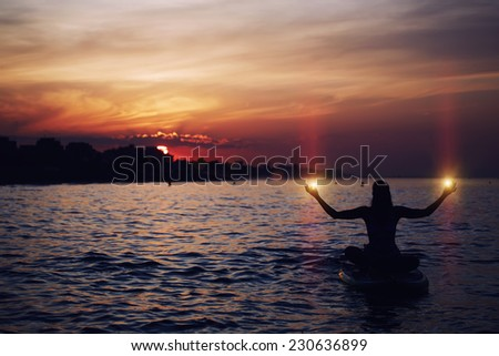 Silhouette of woman holding lights in the hands during sup yoga meditation, yoga training in harmony with nature, silhouette of paddle board yoga performed by beautiful woman, spiritual concept  - stock photo