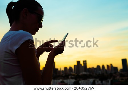 Silhouette of woman in the city using her mobile device. - stock photo