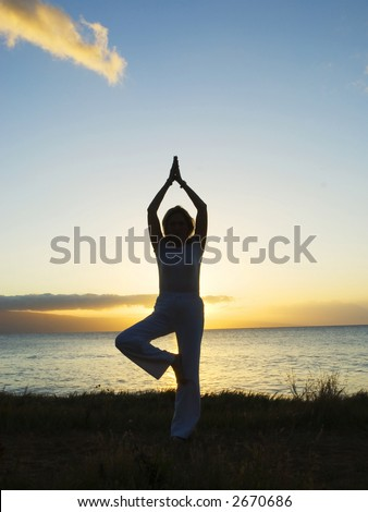 silhouette of woman in traditional pose at sunset
