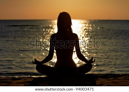 Silhouette of woman in yoga lotus meditation position front to seaside - stock photo