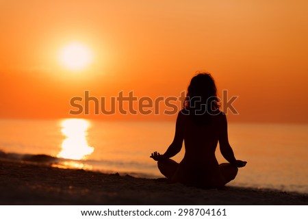 Silhouette of woman in yoga lotus meditation position front to seaside on sunrise - stock photo