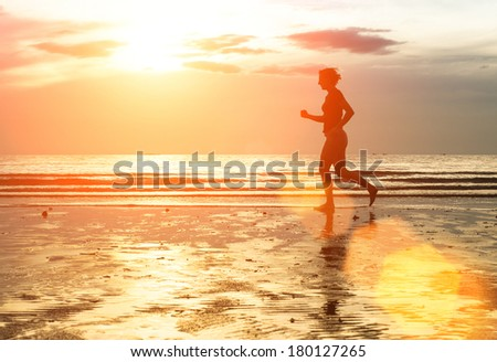 Silhouette of woman jogger at sunset on seashore.