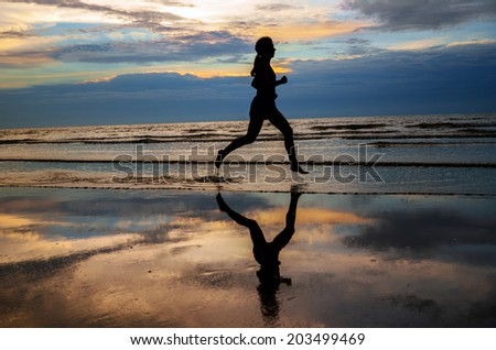 Silhouette of woman jogger running on sunset beach with reflection, fitness and healthy life concept  - stock photo