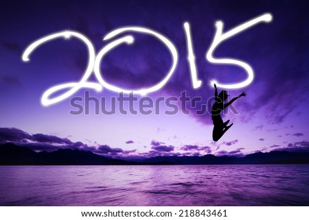 Silhouette of woman jumping and drawing 2015 at sunset - stock photo