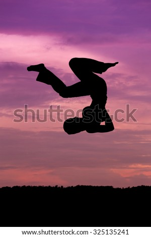 Silhouette of woman jumping at sunset - stock photo