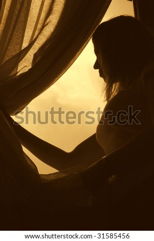 silhouette of woman looking through curtains at open window in hotel,back lit-2