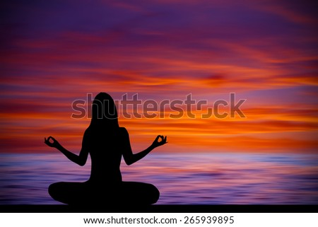 Silhouette of woman making yoga poses on the beach