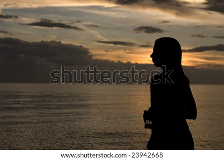silhouette of woman on a beach - stock photo