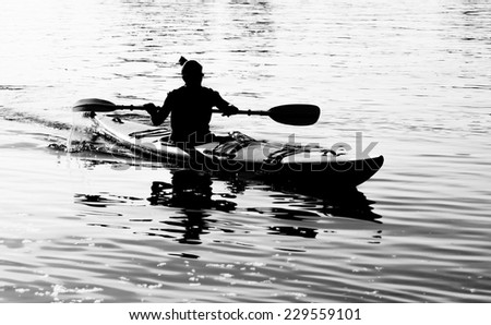 Silhouette of woman on ocean kayak - stock photo