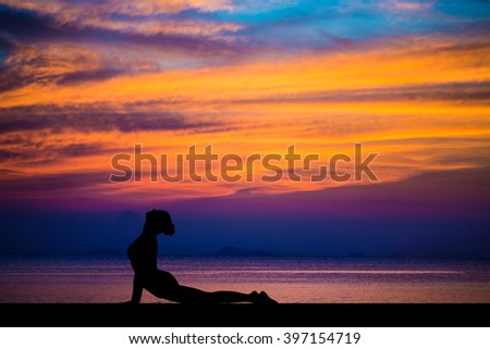Silhouette of woman on the background of the stunning sea and sunset is making yoga exercises