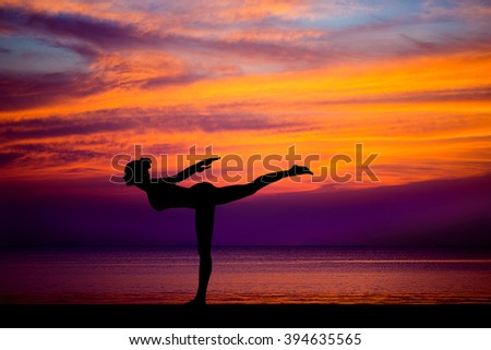 Silhouette of woman on the background of the stunning sea and sunset making yoga asanas exercises