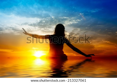 Silhouette of woman performs as yoga exercise on the beach during sunset. digital compositing, colour tone, water reflection and ripple effects. - stock photo