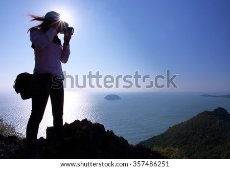 Silhouette of woman photographer take landscape photo on high mountain over the sea. - stock photo