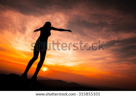 Silhouette of woman posing on rock during the sunset