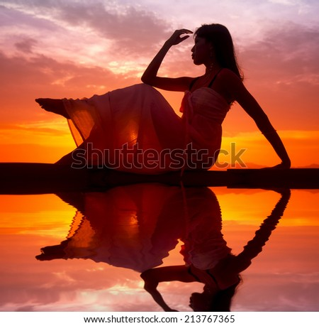 Silhouette of woman posing on the boat during sunset   - stock photo