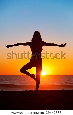 Silhouette of Woman practicing Yoga At Sunset