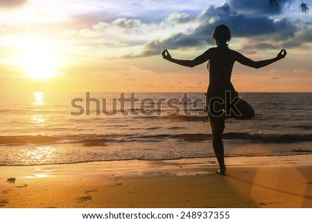 Silhouette of woman practicing yoga during amazing sunset at the seaside. - stock photo