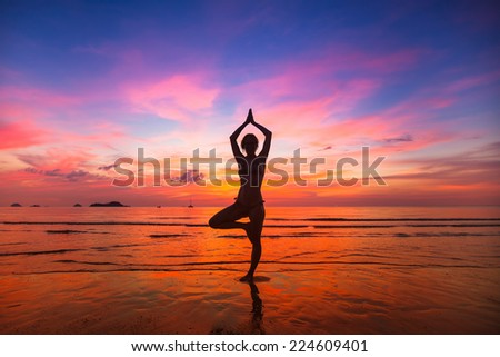 Silhouette of woman practicing yoga during sunset at the seaside. - stock photo