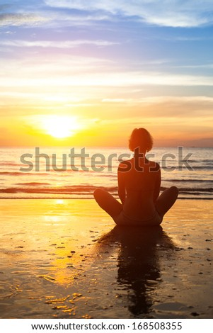 Silhouette of woman practicing yoga on the beach during sunset.