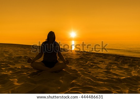 Silhouette of woman practicing yoga on the beach, sunset over the sea