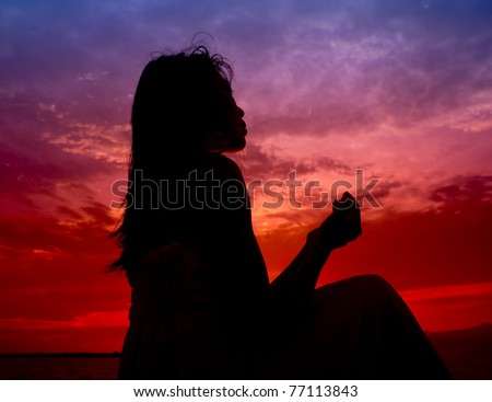 silhouette of woman praying during sunset - stock photo