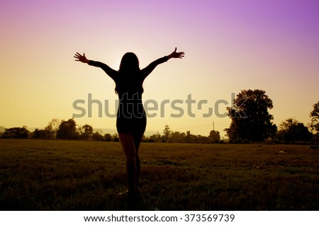 Silhouette of woman praying over beautiful sky and sunset background - stock photo