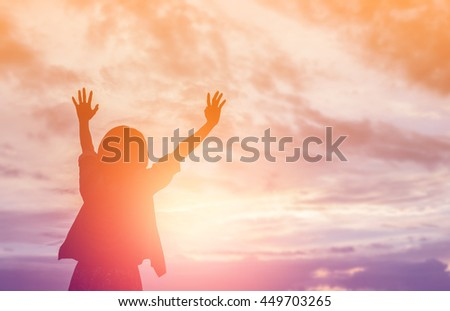 Silhouette of woman praying over beautiful sky background - stock photo