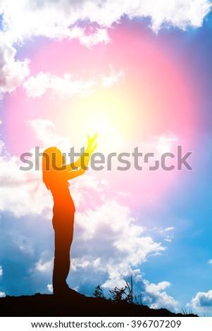 Silhouette of woman praying over beautiful sunrise background - stock photo