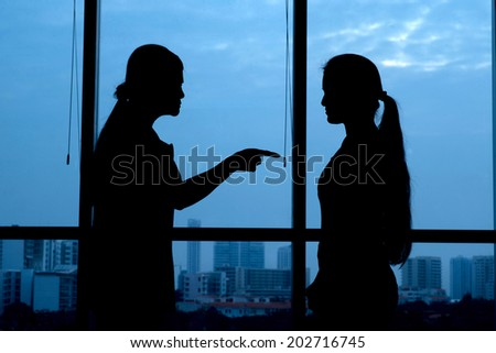 Silhouette of woman punishing her teenage daughter: generation conflict - stock photo