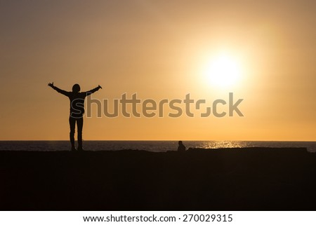Silhouette of woman raising hands to sun at sunset. - stock photo