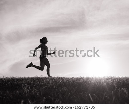 Silhouette of woman running - stock photo