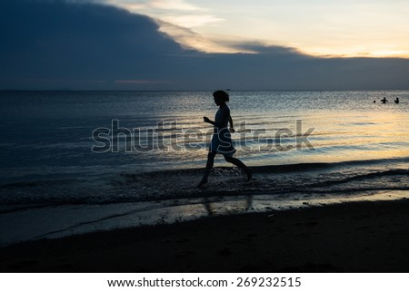 silhouette of woman running on the beach, sunset time - stock photo