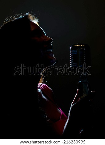 Silhouette of woman singing into vintage microphone. - stock photo