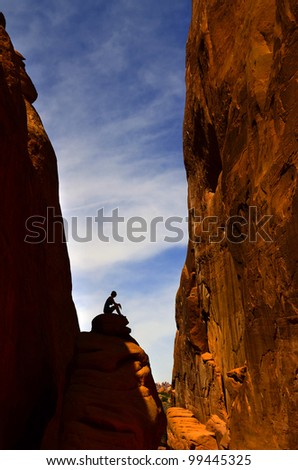 Silhouette of woman sitting on stone in rock canyon in Arches National Park - stock photo