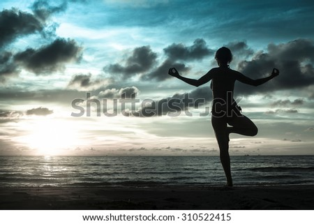 Silhouette of woman standing at yoga pose on the beach during an amazing sunset in cold gray-blue tones. Meditation, balance, harmony and tranquility concept.
