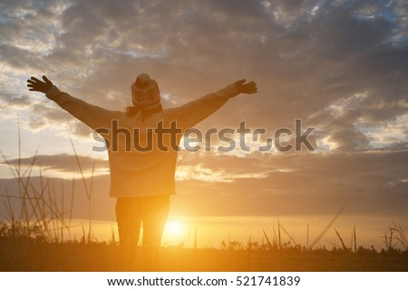 Silhouette of woman standing on field during sunset.