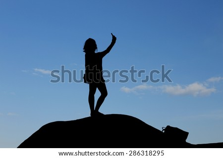 silhouette of woman take her photo selfie by smartphone on top of the hill
