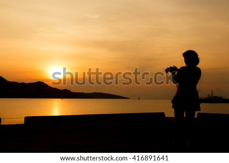 silhouette of woman using the digital camera take photho when sunrise-2