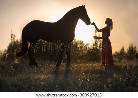 Silhouette of woman with her horse. - stock photo