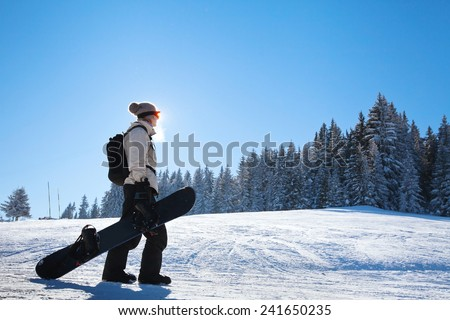 silhouette of woman with snowboard on the ski slope - stock photo